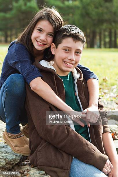 Portrait of brother and sister (12-13) outdoors