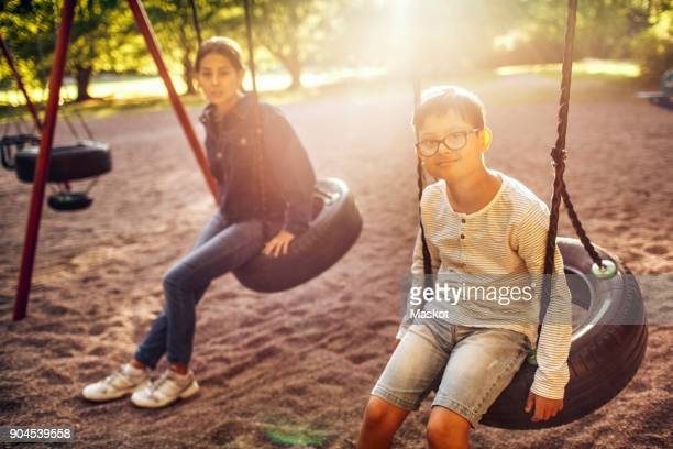 Portrait of brother and sister sitting on swing at park during sunny day