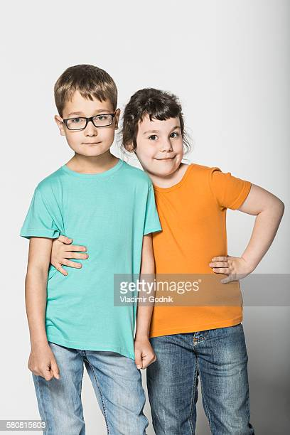Portrait of brother and sister standing arm around against white background