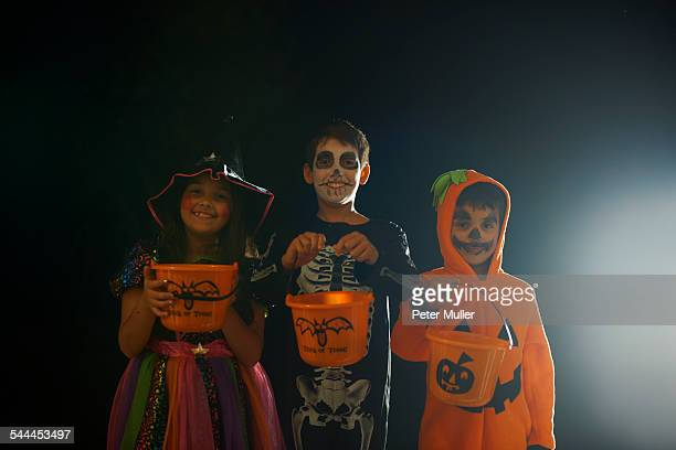 portrait of brothers and sister wearing halloween costumes holding trick or treat buckets - halloween kids stock photos and pictures