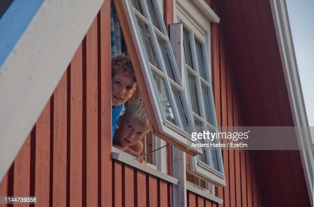 portrait of brothers peeking through window of house - norway stock pictures, royalty-free photos & images