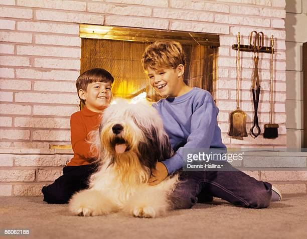 Portrait of brothers playing with dog