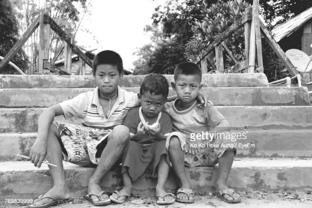 portrait of brothers sitting on steps in park - ko ko htike aung stock pictures, royalty-free photos & images