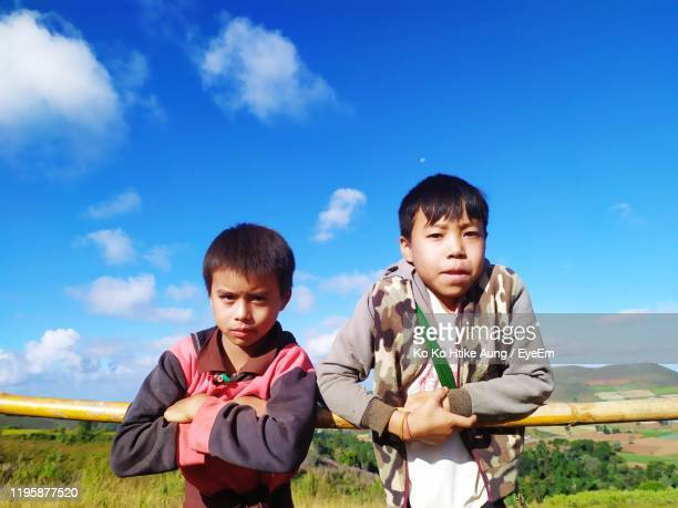 portrait of brothers standing by bamboo against sky - ko ko htike aung stock pictures, royalty-free photos & images