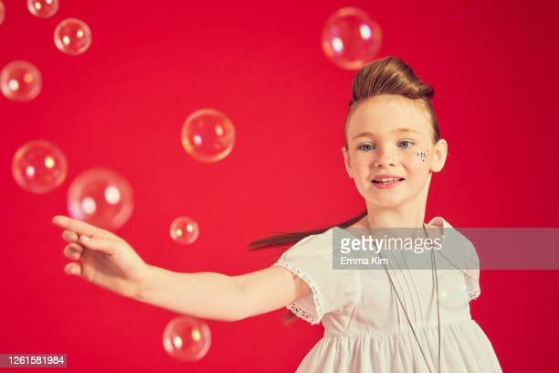 portrait of brunette girl wearing romantic white dress on red background, surrounded by soap bubbles. - white dress stock pictures, royalty-free photos & images