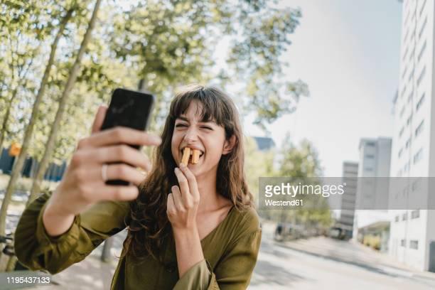 portrait of brunette woman, taking a selfie, rabbit teeth with french fries - schnellimbiss stock-fotos und bilder