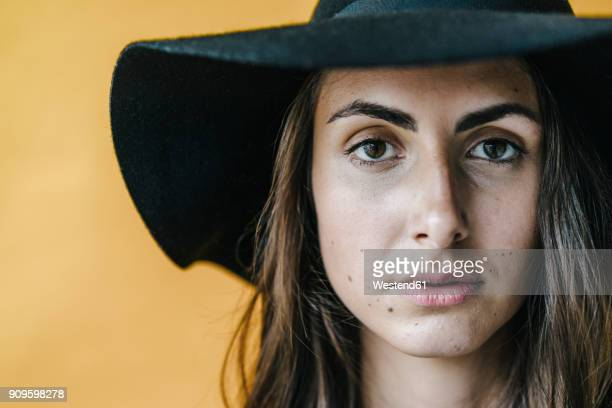 portrait of brunette young woman wearing a floppy hat - mole stock photos and pictures