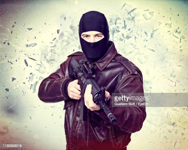 portrait of burglar shooting with rifle against wall - obscured face stock pictures, royalty-free photos & images