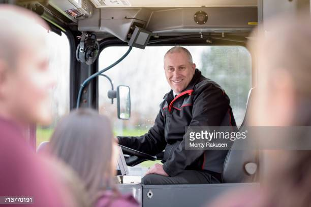 Portrait of bus driver with passengers boarding electric bus