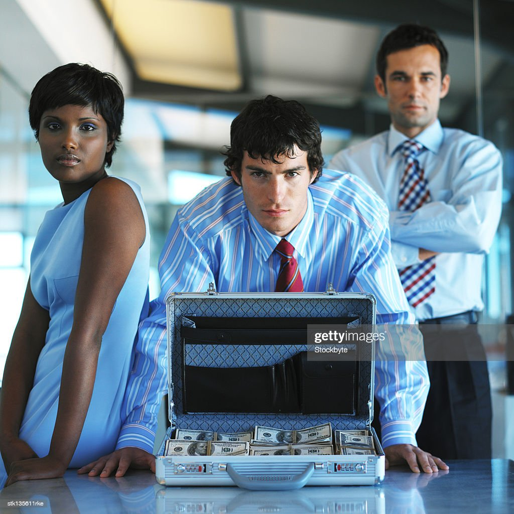 portrait of business executives behind an open briefcase full of money : Stock Photo
