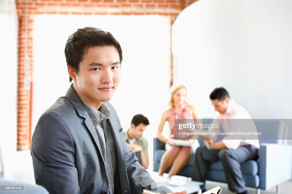 portrait of business man in foreground of group : Stock Photo