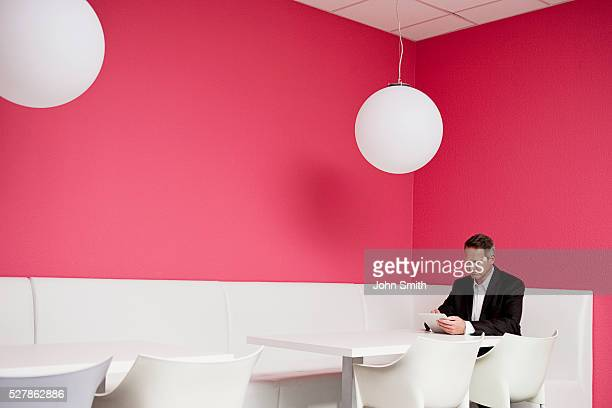 Portrait of business man sitting in canteen and using digital tablet