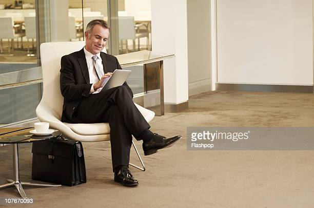portrait of business man using computer tablet - double breasted stock pictures, royalty-free photos & images