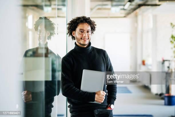 portrait of business manager holding laptop - hell beleuchtet stock-fotos und bilder