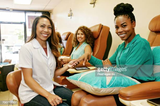 portrait of business owner and customers in nail salon - black pedicure fotografías e imágenes de stock