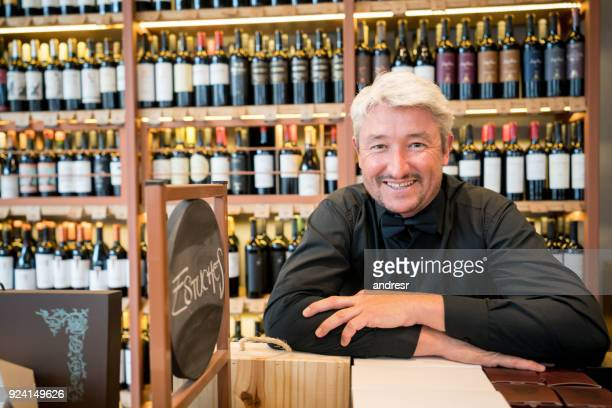 Portrait of business owner leaning on a shelf at his winery looking at camera smiling