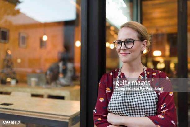portrait of business owner standing outside cafe - unternehmer stock-fotos und bilder