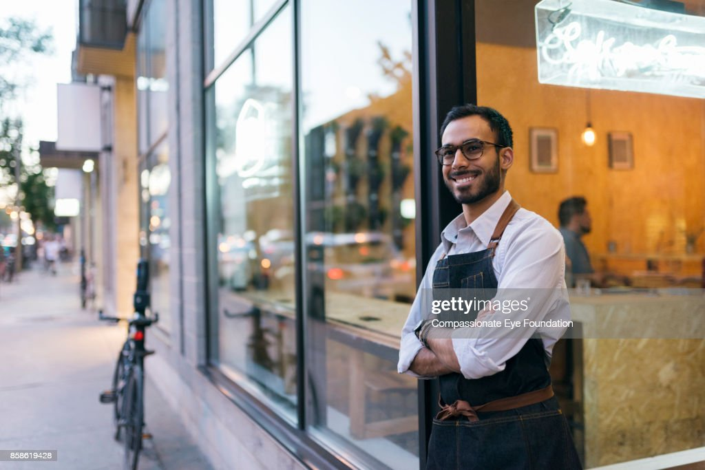 Portrait of business owner standing outside cafe : Stock-Foto