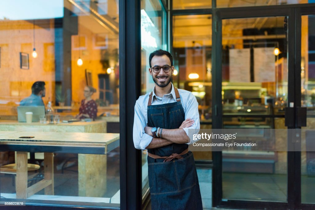 Portrait of business owner standing outside cafe : Stock Photo
