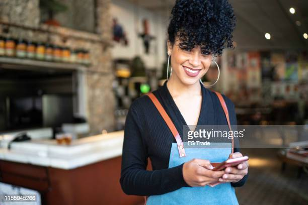 portrait of business owner using phone and looking at camera - part of a series stock pictures, royalty-free photos & images