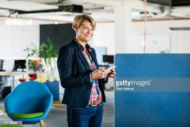 portrait of business owner using smartphone - directrice photos et images de collection