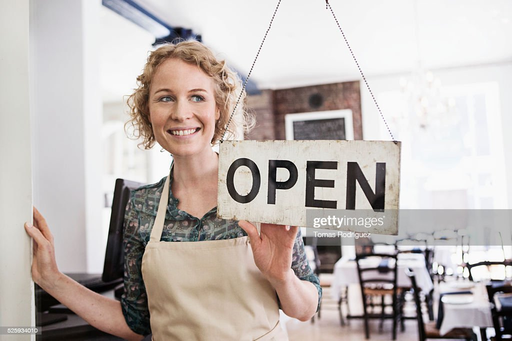 Portrait of business owner with open sign : Bildbanksbilder