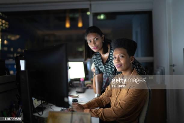 portret van zakenpartners die laat op kantoor werken - mensen op de achtergrond stockfoto's en -beelden