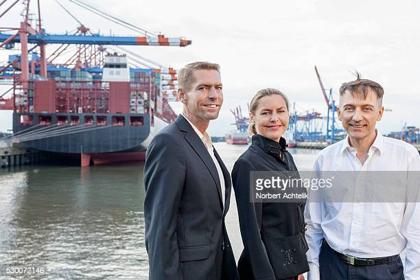 Portrait of business people at harbour and smiling, Hamburg, Germany
