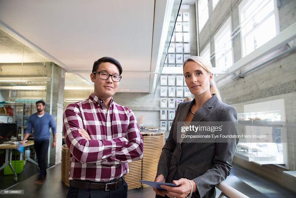 Portrait of business people in busy lobby : Stock Photo