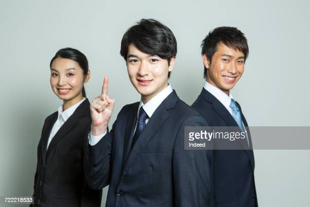 Portrait of business people, pointing finger up