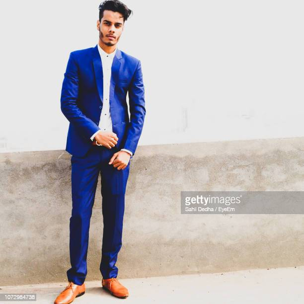 portrait of business standing against wall - blue suit stock pictures, royalty-free photos & images