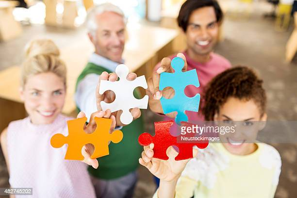 Portrait Of Business Team Holding Jigsaw Pieces