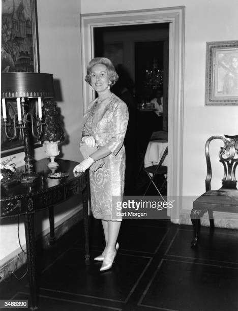 Portrait of business woman, executive, and beautician Estee Lauder as she stands in front of a curved table, mid 1960s.