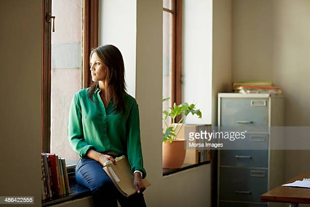 Portrait of business woman sitting in windowsill