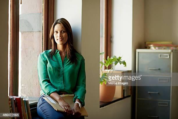 Portrait of business woman sitting in windowsill