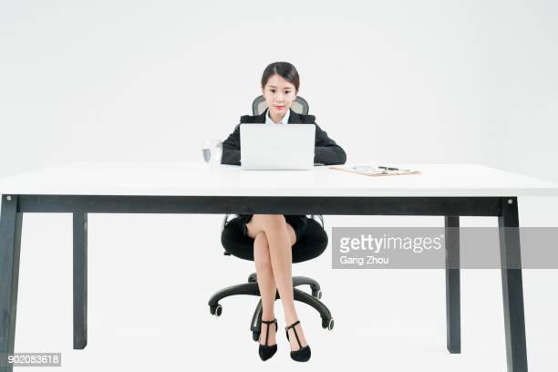 portrait of business woman working at desk against white background - front view stock pictures, royalty-free photos & images