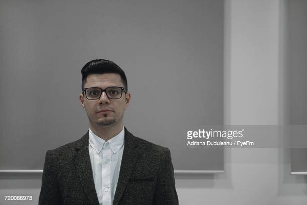 portrait of businessman against gray wall - adriana duduleanu stock photos and pictures