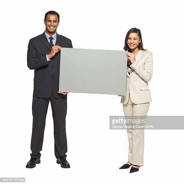 Portrait of businessman and businesswoman holding blank card between them