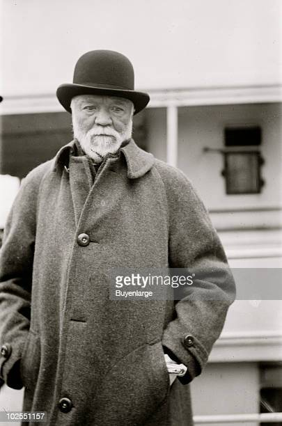 Portrait of businessman and industrialist Andrew Carnegie wearing a bowler hat and heavy coat 1912 He stands with his hands in his pockets and...