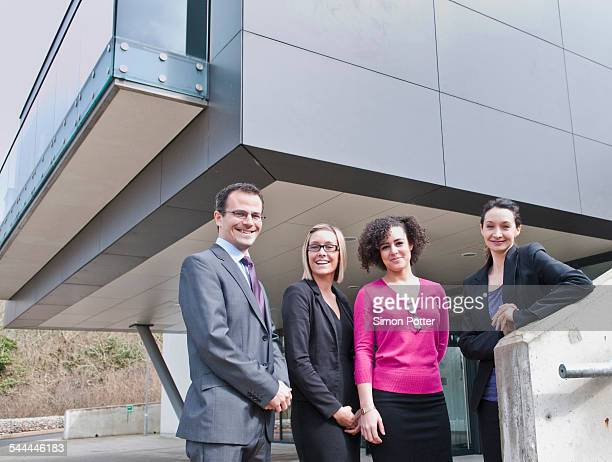Portrait of businessman and three businesswomen outside office building