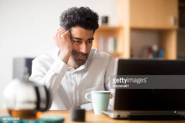 Portrait of businessman at desk looking at laptop