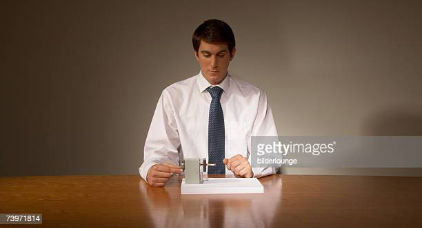 portrait of businessman at desk using pencil sharpener