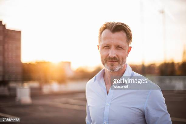 portrait of businessman at sunset - gegenlicht stock-fotos und bilder