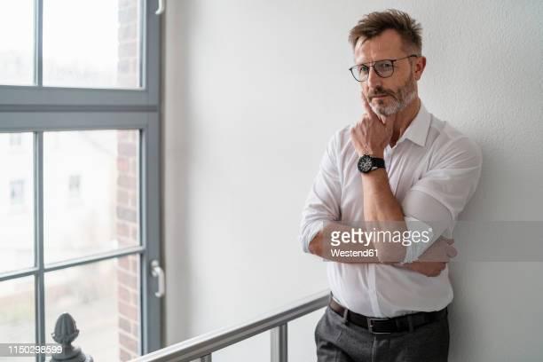 portrait of businessman at the window in office - 袖を折った袖まくり ストックフォトと画像
