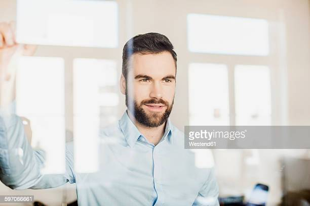 Portrait of businessman behind glass wall