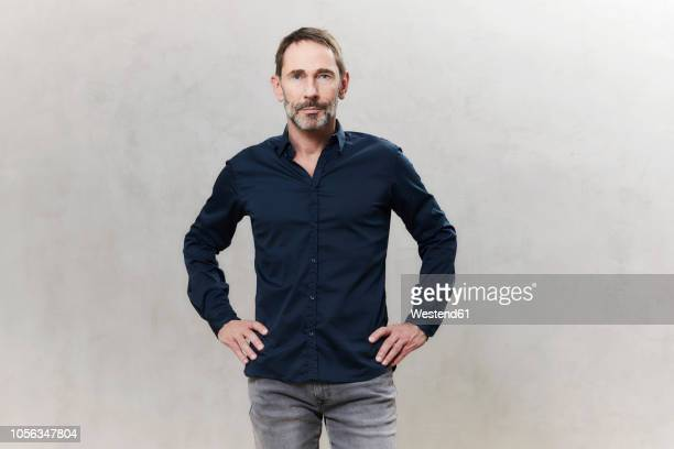 portrait of businessman, dark blue shirt, waist up - handen op de heupen stockfoto's en -beelden