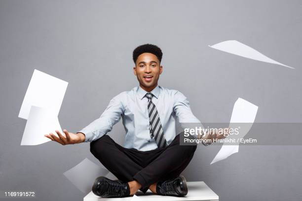 portrait of businessman doing yoga while sitting on table against gray background - serene people stock pictures, royalty-free photos & images