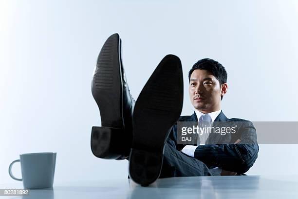 Portrait of businessman, feet resting on desk, China, Beijing