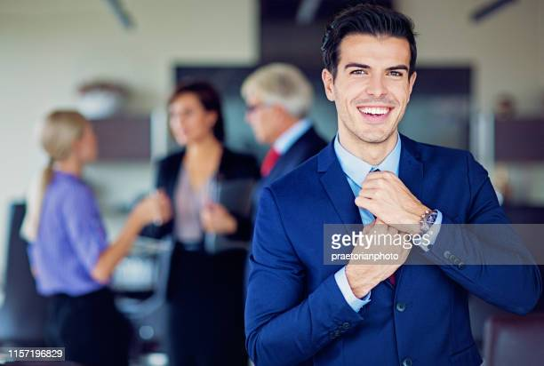 portrait of businessman fixing his tie in the office - adjusting necktie stock pictures, royalty-free photos & images