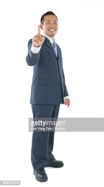 Portrait Of Businessman Gesturing While Standing Against White Background